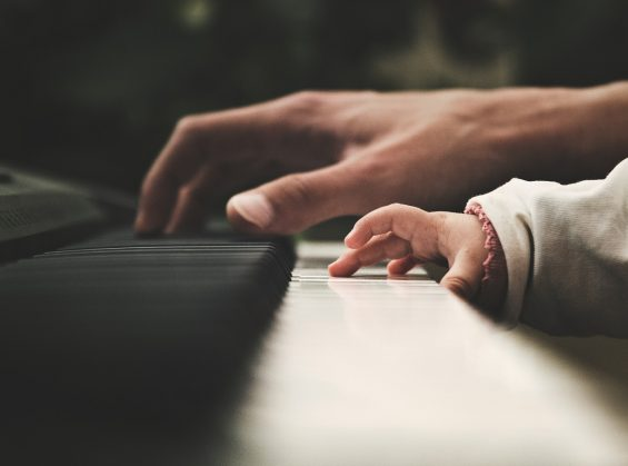 Adult and baby playing the piano